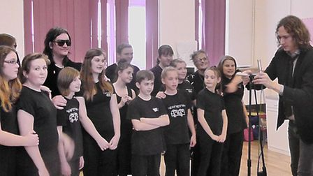 VOCAL SUPPORT: Dan Hawkins, far right, and Ed Graham of The Darkness with youngsters from Lowestoft
