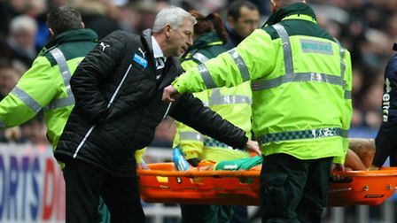 Norwich City midfielder Anthony Pilkington is consoled by Newcastle's Alan Pardew as he is carried off in the club's 2-1...
