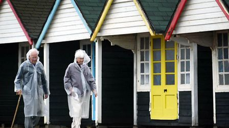 An elderly couple stroll past empty beach huts. Pension age set to rise again.
