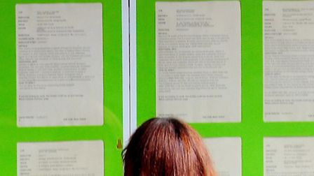 File photo dated 17/8/2011 of a woman look at information boards in the window of the Job Centre Plu