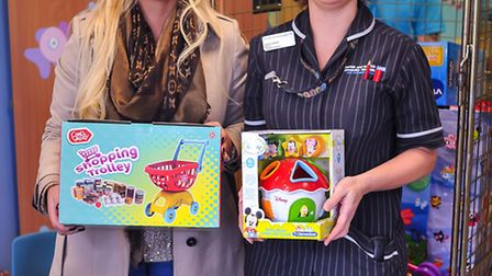 Lisa Unstead handing over trolleys full of toys to Emma Dolman for the children's ward at the N&N. P