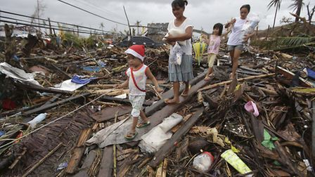 Survivors walk in typhoon ravaged Tacloban city, Leyte province, central Philippines on Tuesday, Nov