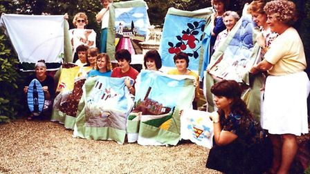 The ladies show off their quilts.