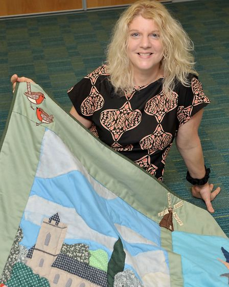 Alison Sutton, Area Library Manager, holding a quilt.
