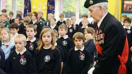 Veteran Royal Marine Len Bloomfield stands with the pupils at St Mary's Community Primary School for