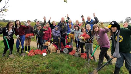 Stalham High School pupils and Stalham in Bloom members planting daffodil bulbs to celebrate the Que