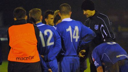 Wroxham manager Pavel Guziejko, 3rd right, talks to his players at the end of their 5-2 defeat to Ne