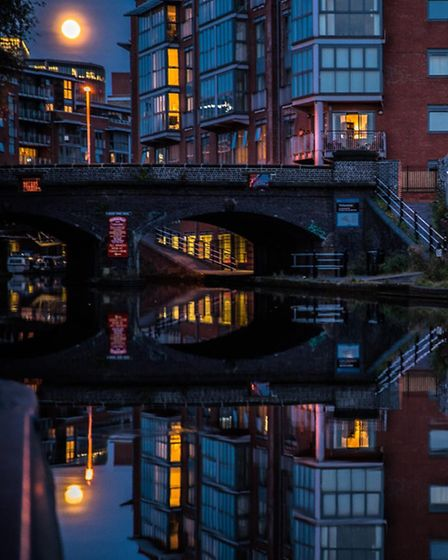 Full moon rising over the Birmingham mainline canal towards the new flats at Sherbourne wharf. PHOTO