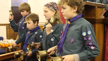 Bell ringing Cubs entertaining the congregation at West Runton Scouts' Christingle service. Photo: K