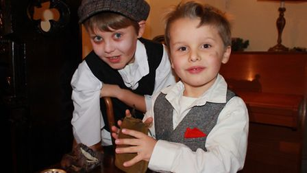 Tiny Tim (eight-year-old Christian Rondel) watches as a well-to-do Dickensian youngster (Christian's