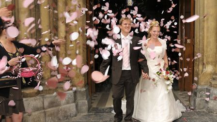 Confetti petals are sprinkled over the newly married couple open leaving the church