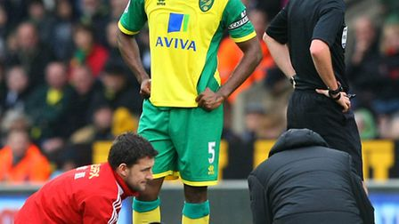 Norwich City captain Sebastien Bassong casts a worried look towards Swansea's Nathan Dyer after the