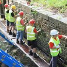 Clearing out old mortar and vegetation from the lock wall