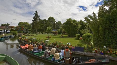 A 'cornet' boat cruises by one of Amiens' floating gardens in Somme ©Jonathan/fotolia