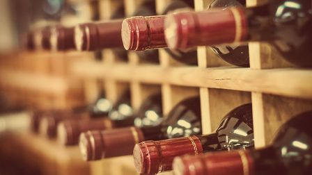 Red wine bottles stacked on wooden racks (c) Getty Images