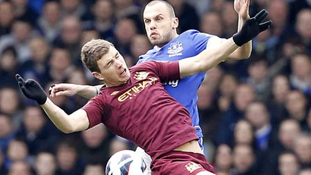 Everton's Johnny Heitinga and Manchester City's Edin Dzeko (front) battle for the ball during a Barc