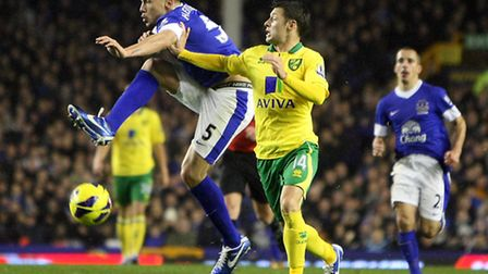 John Heitinga of Everton and Wes Hoolahan of Norwich in action during the Barclays Premier League ma