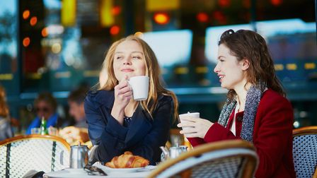 Two friends catching up at a Parisian cafe (c) encrier/Getty Images