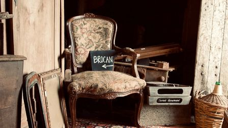 The brocante sign rests on a beautifully upholstered armchair ©Melissa Raton