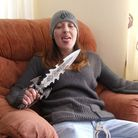 Dennehy jovially sticking her tongue out as she brandishes a jagged knife with handcuffs attached to