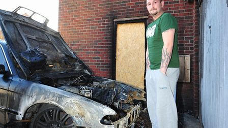 Chris Gray next to his burn out car. The car burst into flames on his drive and nearly burnt his hom