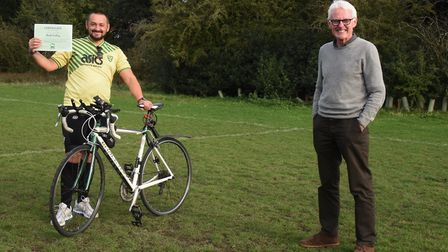 Fundraiser Matt Colley and Sir Norman Lamb, with the certificate Matt received for cycling over 500