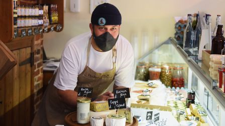 Charlie Hodson leaning over the cheese counter in his new delicatessen in Aylsham.
