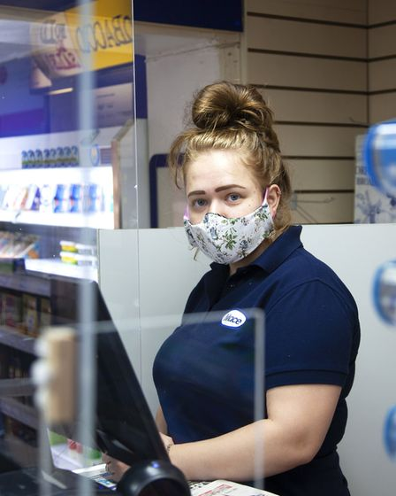 Chloe Morter serves in the Coltishall Post Office and Mace, packing up deliveries to go out to those
