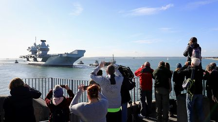 The Royal Navy aircraft carrier HMS Queen Elizabeth arrives back in Portsmouth Naval Base after taki