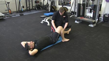 Mark Bone, owner of Phoenix Gym Norwich, helping a client in the studio before lockdown. Photo: Must