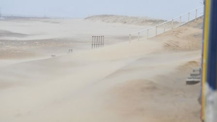 Sand is blown off the beach at Southwold during the high winds that have battered the UK.
