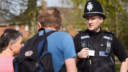 PC Peter Baitey chats one couple out exercising during his patrol of Eaton Park during the coronavir