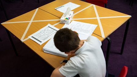 Social distancing measures as a child studies on a marked table. Photo: Jacob King/PA Wire
