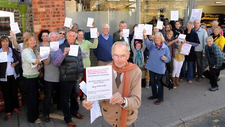 John Veitch, who has died in a crash in Suffolk, holds up a poster outside the new Tesco Express sto