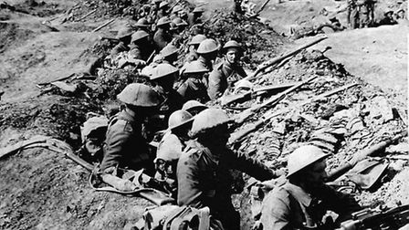 Library filer dated 01/07/1916 of British infantrymen occupying a shallow trench in a ruined landsca
