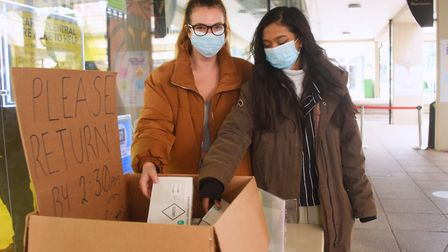 Students, Alex Hickey-Wilson, 20, left, and Monsai Seereekissoon, 20, collect their testing kits at