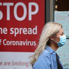 A woman wearing a face mask walking past a COVID sign