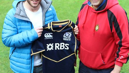 Alistair Price (left) presenting the shirt to director of sport Phillip Webb.
