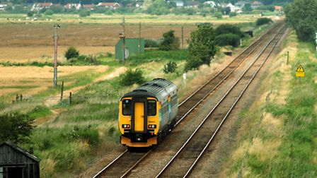 Train from Lowestoft to Norwich on the Wherry Line makes its way towards Reedham beside the New CutP