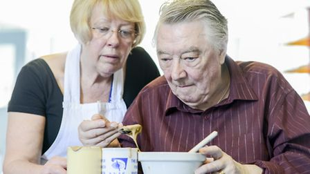 Visually impaired people having cookery lessions - Ron Stokes makes a pudding in a mug with help fro