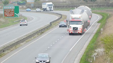 A wide load is escorted along the A11 from Snetterton.