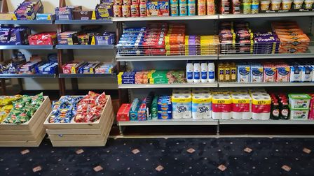 Shelves of tinned and packets of food as well as toilet rolls and other essentials in pub function room with patterned carpet