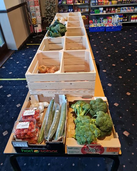 Crates and boxes of fresh fruit and vegetables on floor of pub for sale