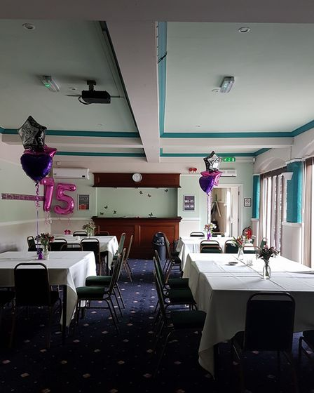 Tables with white cloths on set up for dinner in pub function room with blue patterned carpet