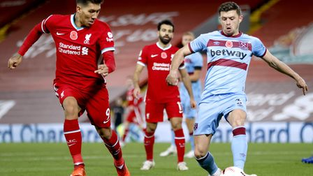 Liverpool's Roberto Firmino (left) and West Ham United's Aaron Cresswell battle for the ball during