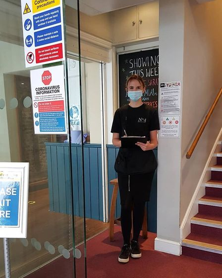 A cinema greeter with PPE, ready to welcome customers back to Abbeygate Cinema in Bury St Edmunds: Abbeygate Cinema