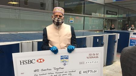 The moment champion lap-walker Dabirul hands over cheque to Royal London Hospital for the NHS. Pictu