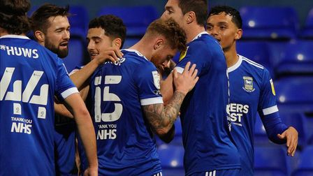 Town players celebrate with Teddy Bishop after his goal to secure victory. Picture: STEVE WALLER