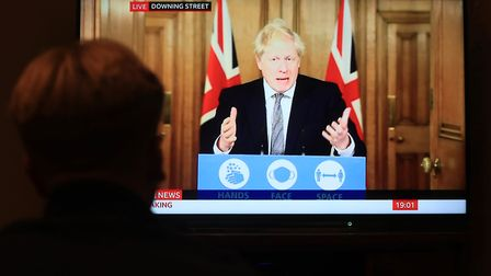 A member of the public watches a press conference with Prime Minister Boris Johnson Picture: Mike Egerton/PA Wire