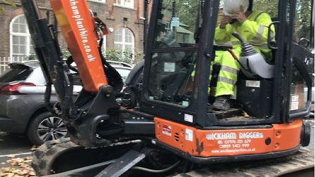 Mechanical digger in Rochelle Street, a few yards from Arnold Circus, driver's face hidden,working o